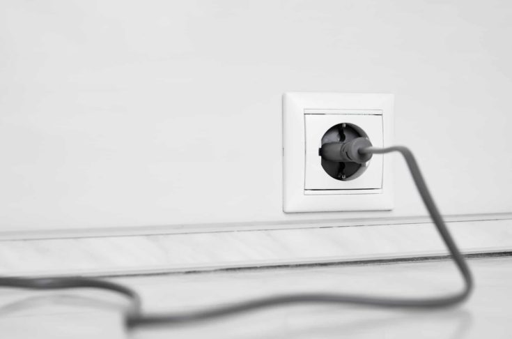 Electric white socket and one plugged in power cord on white wall background