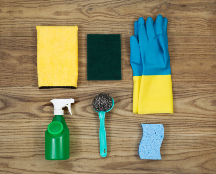 Overhead view of house cleaning materials placed on rustic wood. Items include sponge, rubber gloves, stainless steel pad, spray bottle, microfiber rag, and scrub pad.
