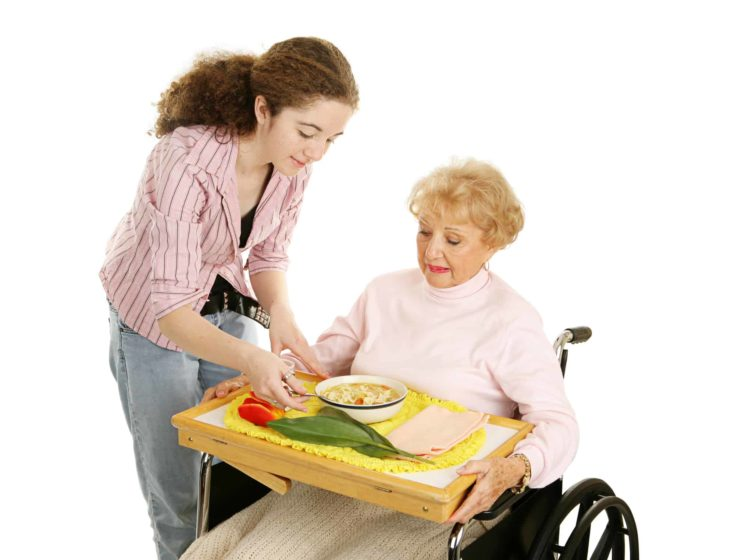 Teen volunteer brings lunch to a disabled senior woman. Isolated on white.