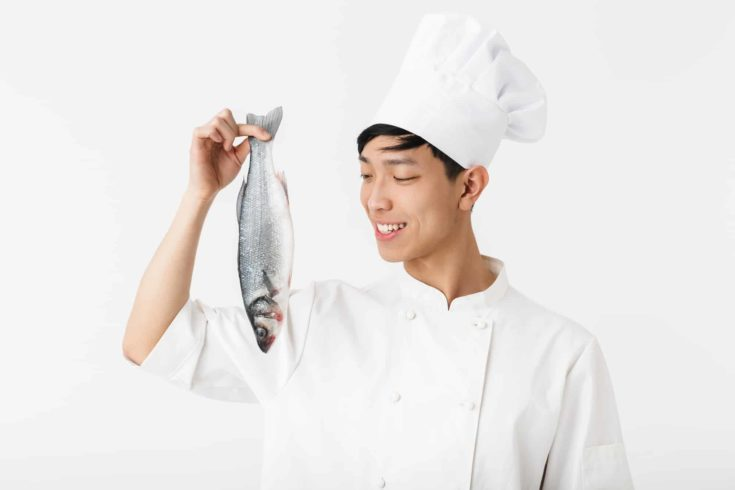 Image of young positive chief man in white cook uniform and hat smiling while holding raw fresh fish isolated over white background