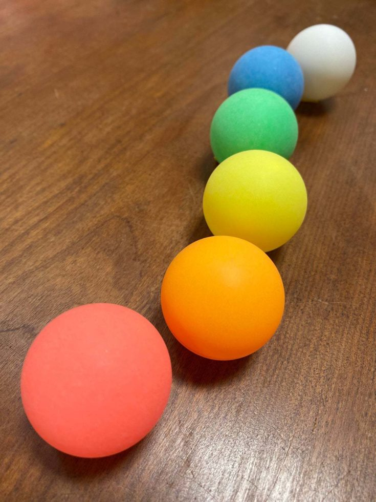 Colored Ping Pong balls on wooden table